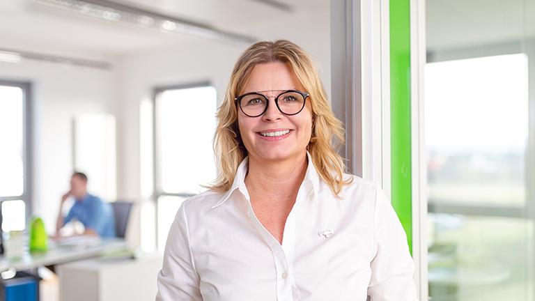 Lächelnde Frau im Unternehmensgebäude